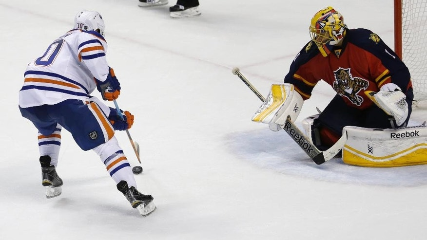 Edmonton Oilers right wing Nail Yakupov, left, prepares to shoot the game-winning goal against Florida Panthers goalie Roberto Luongo, right, during a shootout in an NHL hockey game, Saturday, Jan. 17, 2015, in Sunrise, Fla. The Oilers defeated the Panthers 3-2 in a shootout. (AP Photo/Lynne Sladky)