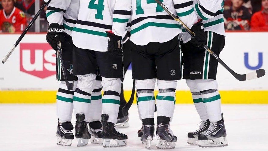 Dallas Stars players celebrate a goal scored by center Tyler Seguin against the Chicago Blackhawks during the first period of an NHL hockey game in Chicago, Sunday, Jan. 18, 2015. (AP Photo/Kamil Krzaczynski)