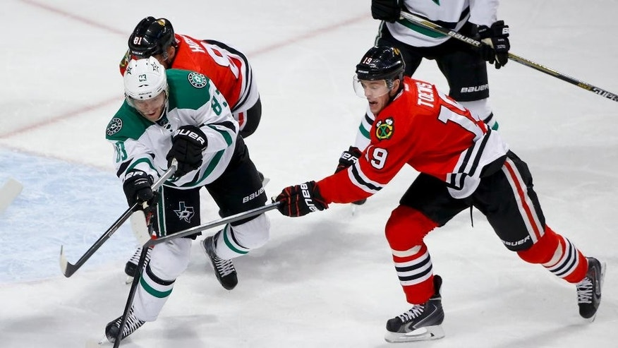 Dallas Stars right wing Ales Hemsky (83) battles for the puck with Chicago Blackhawks center Jonathan Toews (19) during the first period of an NHL hockey game in Chicago, Sunday, Jan. 18, 2015. (AP Photo/Kamil Krzaczynski)