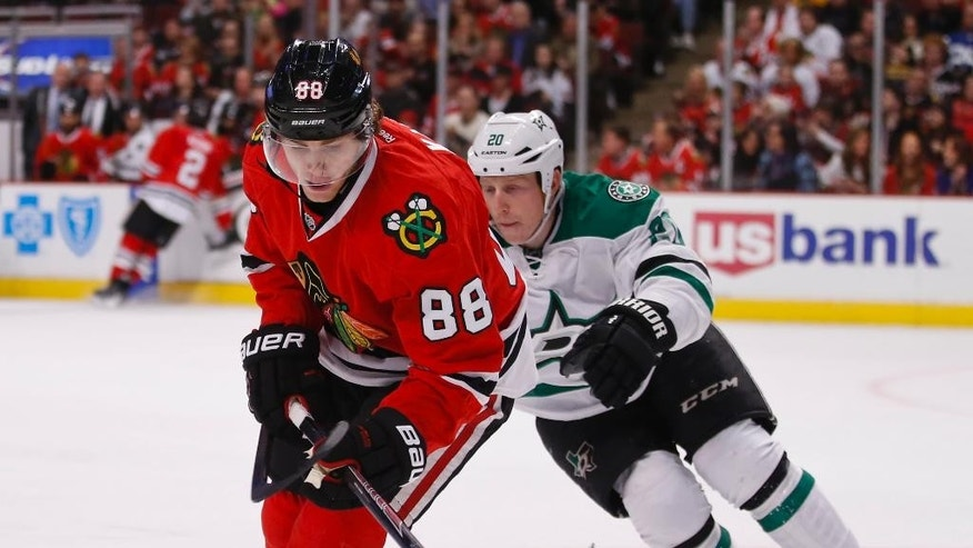 Chicago Blackhawks right wing Patrick Kane (88) keeps the puck away from Dallas Stars center Cody Eakin (20) during the first period of an NHL hockey game in Chicago, Sunday, Jan. 18, 2015. (AP Photo/Kamil Krzaczynski)