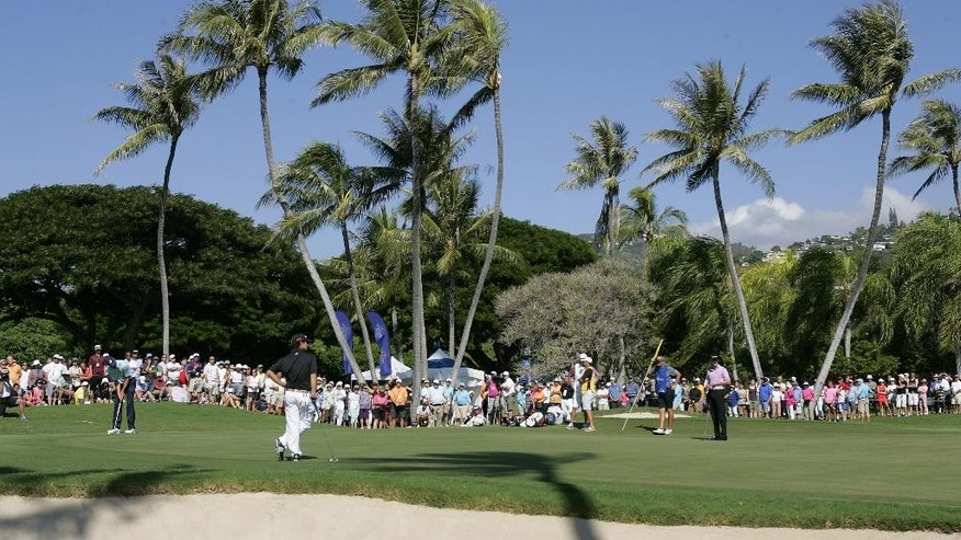 Matt Kuchar, left, putts on the third green as Brian Harman, second from left, and Jimmy Walker, right, wait during the final round of the Sony Open golf tournament, Sunday, Jan. 18, 2015, in Honolulu. (AP Photo/Hugh Gentry)
