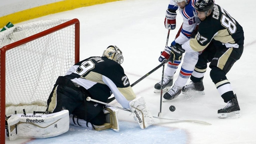 New York Rangers' Rick Nash (61) cannot get a shot past Pittsburgh Penguins goalie Marc-Andre Fleury (29) with Sidney Crosby (87) defending during the first period of an NHL hockey game in Pittsburgh, Sunday, Jan. 18, 2015. (AP Photo/Gene J. Puskar)