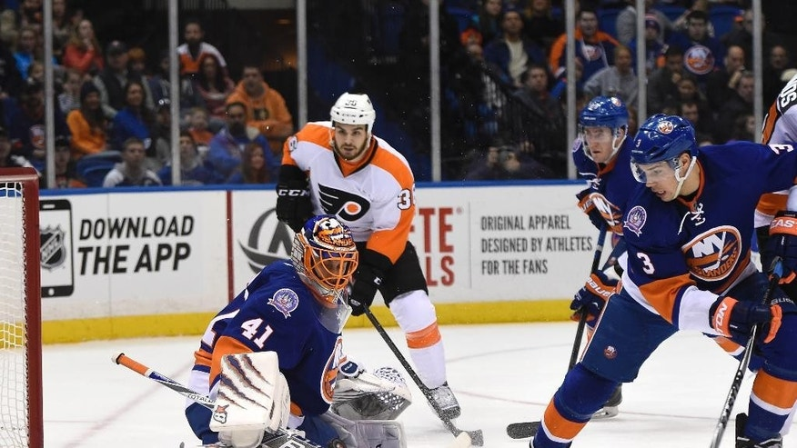 New York Islanders goalie Jaroslav Halak (41) blocks a shot on goal as New York Islanders defenseman Travis Hamonic (3) and Flyers center Zac Rinaldo (36) skate near the net in the first period of an NHL hockey game at Nassau Coliseum on Monday, Jan. 19, 2015, in Uniondale, N.Y. (AP Photo/Kathy Kmonicek)