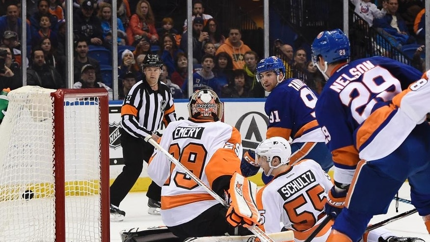 New York Islanders center John Tavares (91) shoots the puck past Philadelphia Flyers goalie Ray Emery (29) and  defenseman Nick Schultz (55) to score as  Islanders center Brock Nelson (29) looks on in the second period of an NHL hockey game at Nassau Coliseum on Monday, Jan. 19, 2015, in Uniondale, N.Y. (AP Photo/Kathy Kmonicek)