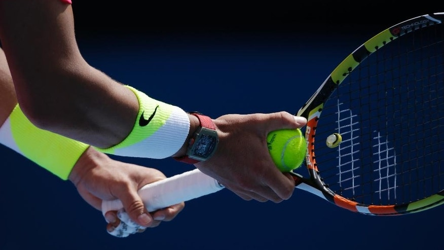 Rafael Nadal of Spain holds the racket as he plays Mikhail Youzhny of Russia during their first round match at the Australian Open tennis championship in Melbourne, Australia, Monday, Jan. 19, 2015. (AP Photo/Bernat Armangue)