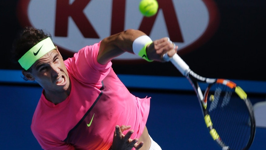 Rafael Nadal of Spain serves to Mikhail Youzhny of Russia during their first round match at the Australian Open tennis championship in Melbourne, Australia, Monday, Jan. 19, 2015. (AP Photo/Bernat Armangue)