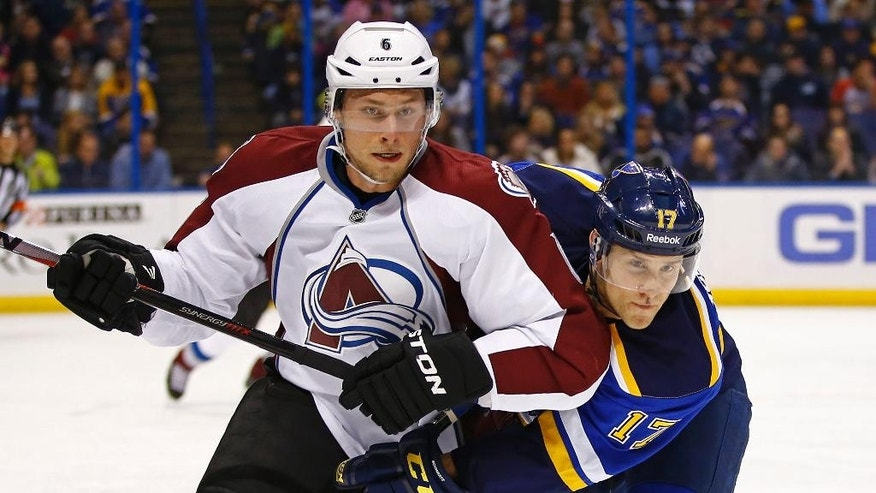 Colorado Avalanche's Erik Johnson, left, and St. Louis Blues' Jaden Schwartz battle for position during the first period of an NHL hockey game Monday, Jan. 19, 2015, in St. Louis.  (AP Photo/Billy Hurst)