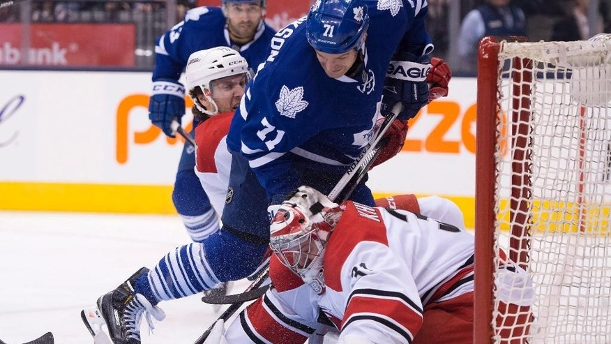 Carolina Hurricanes goaltender Anton Khudobin makes a save on Toronto Maple Leafs right winger David Clarkson (71) as he is hauled down by Hurricanes defenseman Bret Bellemore (73) during second period of an NHL hockey game in Toronto, Monday, Jan. 19, 2015. (AP Photo/The Canadian Press, Frank Gunn)