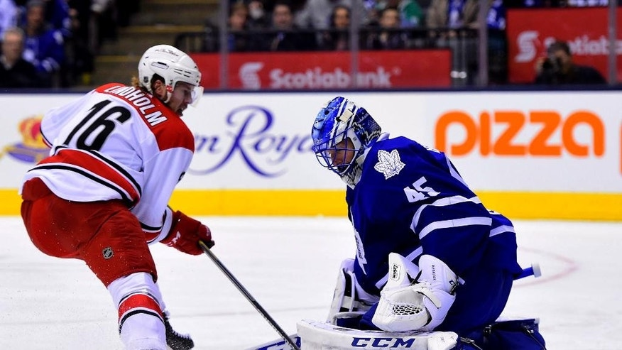 Carolina Hurricanes' Elias Lindholm (16) scores on Toronto Maple Leafs' goalie Jonathan Bernier (45) during first period NHL action in Toronto, Monday, Jan. 19, 2015. (AP Photo/The Canadian Press, Frank Gunn)