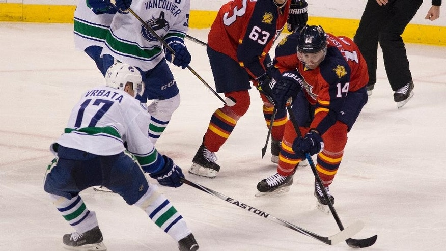 Vancouover Canucks' Radim Vrbata (17) and Florida Panthers' Tomas Fleischmann (14) battle for the puck during the third period of an NHL hockey game in Sunrise, Fla., Monday, Jan. 19, 2015. The Canucks won 2-1. (AP Photo/J Pat Carter)