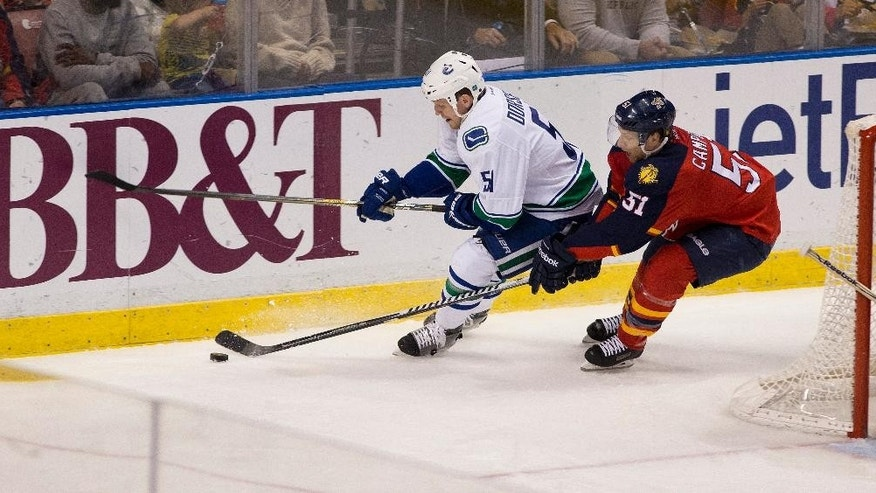 Vancouver Canucks' Derek Dorsett (51) and Florida Panthers' Brian Campbell (51) chase the puck during the second period of an NHL hockey game in Sunrise, Fla., Monday, Jan. 19, 2015.  (AP Photo/J Pat Carter)