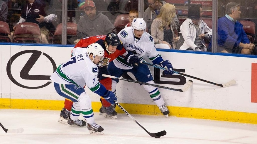 Vancouver Canucks' Alexandre Burrows (14) tries to keep Florida Panthers' Dylan Olsen (4) away from Linden Vey (7) during the second period of an NHL hockey game in Sunrise, Fla., Monday, Jan. 19, 2015.  (AP Photo/J Pat Carter)