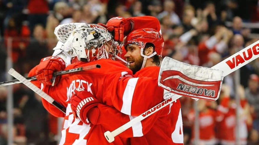Detroit Red Wings left wing Henrik Zetterberg, right, congratulates goalie Petr Mrazek (34) after beating the Minnesota Wild in a shootout during an NHL hockey game in Detroit Tuesday, Jan. 20, 2015. (AP Photo/Paul Sancya)