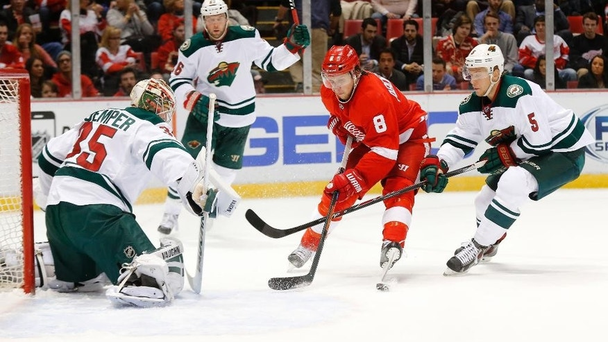 Minnesota Wild goalie Darcy Kuemper (35) blocks a Detroit Red Wings left wing Justin Abdelkader (8) shot as defenseman Christian Folin (5) defends in the second period of an NHL hockey game in Detroit Tuesday, Jan. 20, 2015. (AP Photo/Paul Sancya)