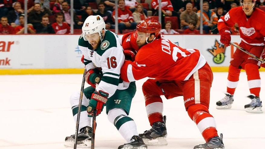 Minnesota Wild left wing Jason Zucker (16) breaks away as Detroit Red Wings defenseman Kyle Quincey (27) defends in the first period of an NHL hockey game in Detroit Tuesday, Jan. 20, 2015. (AP Photo/Paul Sancya)