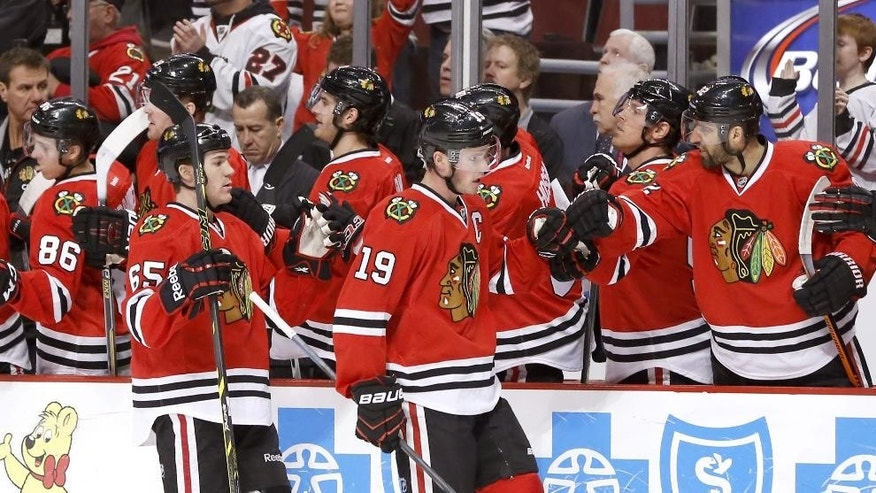 Chicago Blackhawk' Jonathan Toews (19) and Andrew Shaw (65) celebrate Toews' goal with teammates during the first period of an NHL hockey game against the Phoenix Coyotes on Tuesday, Jan. 20, 2015, in Chicago. Shaw would later score the Blackhawks' second goal (AP Photo/Charles Rex Arbogast)