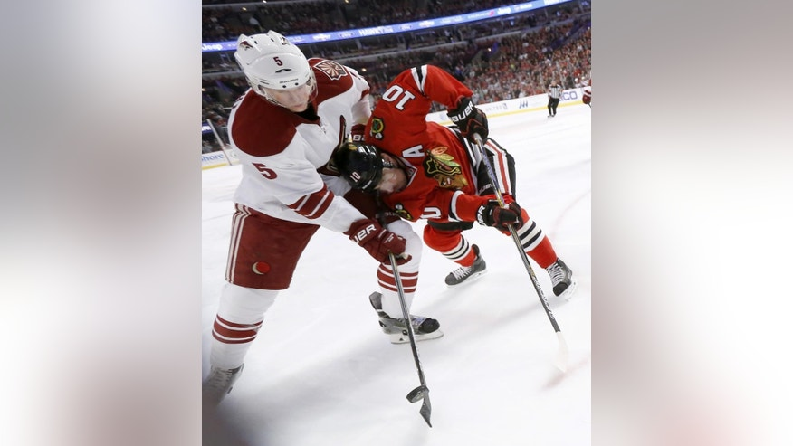 Arizona Coyotes defenseman Connor Murphy (5) and Chicago Blackhawks left wing Patrick Sharp (10) scrap for a loose puck during the first period of an NHL hockey game Tuesday, Jan. 20, 2015, in Chicago. (AP Photo/Charles Rex Arbogast)