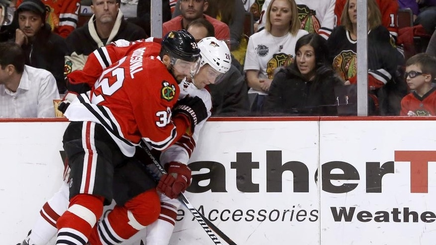 Chicago Blackhawks defenseman Michal Rozsival and Arizona Coyotes left wing Lauri Korpikoski (28) vie for a loose puck during the first period of an NHL hockey game Tuesday, Jan. 20, 2015, in Chicago. (AP Photo/Charles Rex Arbogast)