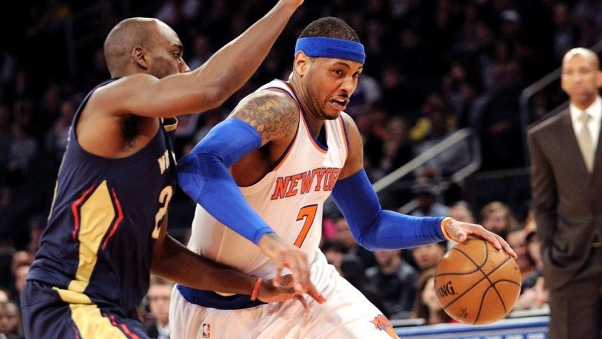 Carmelo Anthony drives to the basket a he is guarded by Quincy Pondexter on Monday, Jan. 19, 2015.