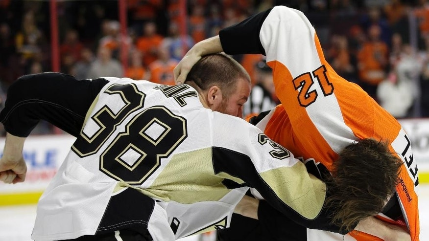 Pittsburgh Penguins' Zach Sill (38) fights with Philadelphia Flyers' Michael Raffl (12), of Austria, during the second period of an NHL hockey game, Tuesday, Jan. 20, 2015, in Philadelphia. (AP Photo/Matt Slocum)