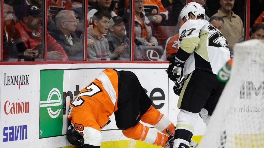 Philadelphia Flyers' Claude Giroux (28) is checked into the boards by Pittsburgh Penguins' Craig Adams (27), of Switzerland, during the second period of an NHL hockey game, Tuesday, Jan. 20, 2015, in Philadelphia. (AP Photo/Matt Slocum)