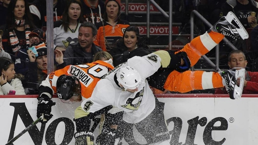 Philadelphia Flyers' Jakub Voracek (93), of the Czech Republic, is sent flying after a collision with Pittsburgh Penguins' Rob Scuderi (4) during the second period of an NHL hockey game, Tuesday, Jan. 20, 2015, in Philadelphia. (AP Photo/Matt Slocum)