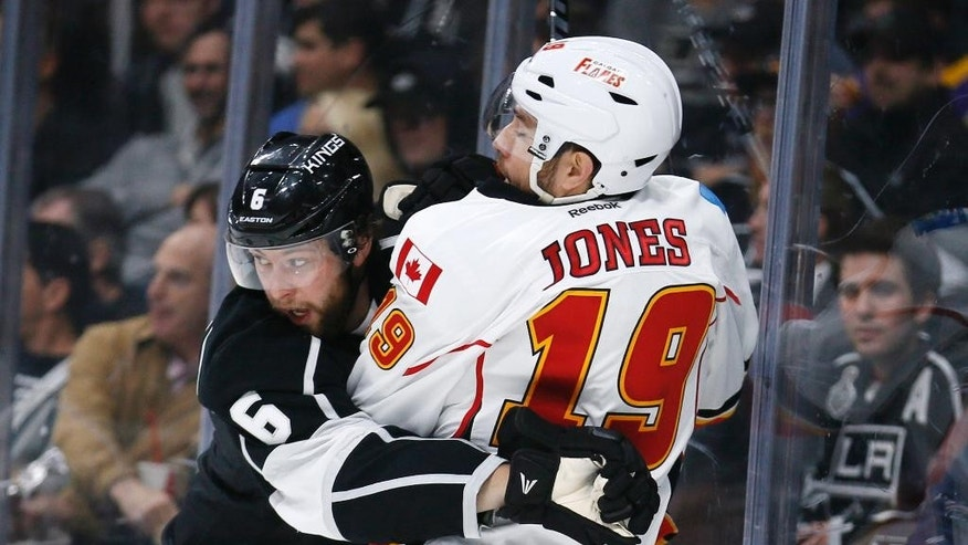 Los Angeles Kings defenseman Jake Muzzin, left, checks Calgary Flames right wing David Jones, right, into the boards during the first period of an NHL hockey game, Monday, Jan. 19, 2015, in Los Angeles. (AP Photo/Danny Moloshok)
