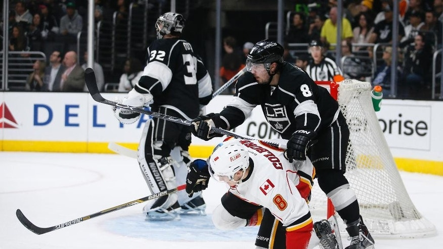 Los Angeles Kings defenseman Drew Doughty gets called for a penalty while he hits Calgary Flames center Joe Colborne with his stick in front of Los Angeles Kings goalie Jonathan Quick during the first period of an NHL hockey game, Monday, Jan. 19, 2015, in Los Angeles. (AP Photo/Danny Moloshok)