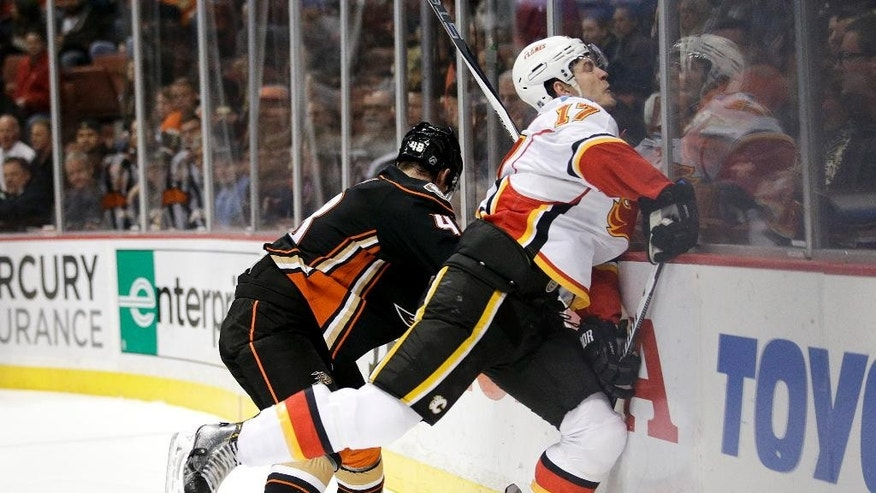 Calgary Flames' Lance Bouma, right, is checked by Anaheim Ducks' Colby Robak during the first period of an NHL hockey game, Wednesday, Jan. 21, 2015, in Anaheim, Calif. (AP Photo/Jae C. Hong)