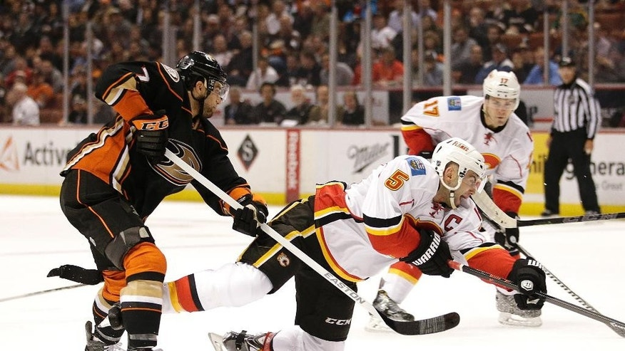 Calgary Flames' Mark Giordano, right, shoots under pressure by Anaheim Ducks' Andrew Cogliano during the first period of an NHL hockey game, Wednesday, Jan. 21, 2015, in Anaheim, Calif. (AP Photo/Jae C. Hong)