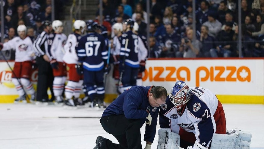 Columbus Blue Jackets goaltender Sergei Bobrovsky (72) is treated on the ice after an injury during the second period of an NHL hockey game against the Winnipeg Jets on Wednesday, Jan. 21, 2015, in Winnipeg, Manitoba. (AP Photo/The Canadian Press, Jason Woods)