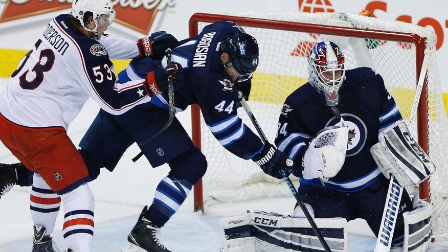 Columbus Blue Jackets' Josh Anderson (53) checks Winnipeg Jets' Zach Bogosian (44) into goaltender Michael Hutchinson (34) during the first period of an NHL hockey game Wednesday, Jan. 21, 2015, in Winnipeg, Manitoba. (AP Photo/The Canadian Press, Jason Woods)