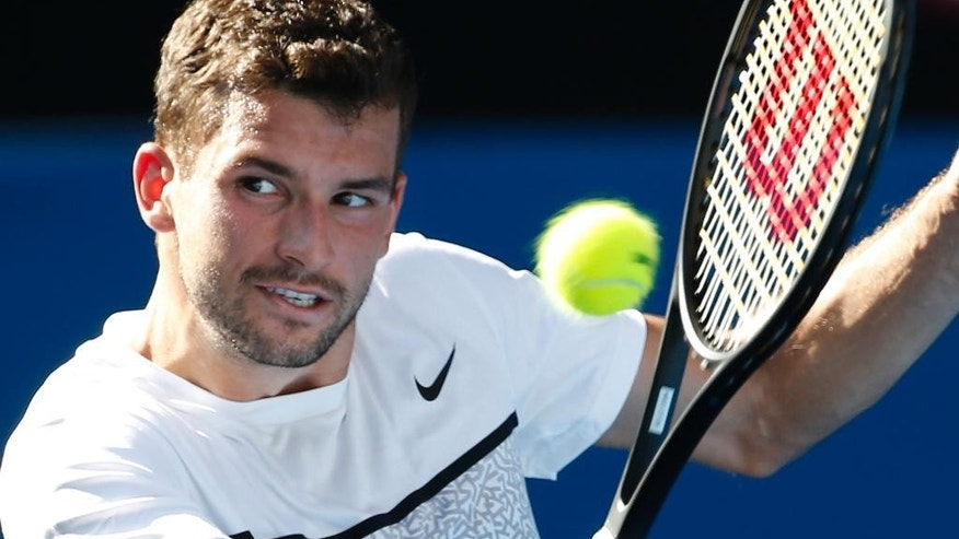 Grigor Dimitrov of Bulgaria makes a backhand return to Lukas Lacko of Slovakia during their second round match at the Australian Open tennis championship in Melbourne, Australia, Wednesday, Jan. 21, 2015. (AP Photo/Vincent Thian)