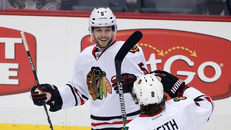 Chicago Blackhawks' David Rundblad (5) celebrates his goal with teammate Duncan Keith (2) during the first period of an NHL hockey game against the Pittsburgh Penguins in Pittsburgh Wednesday, Jan. 21, 2015.(AP Photo/Gene J. Puskar)