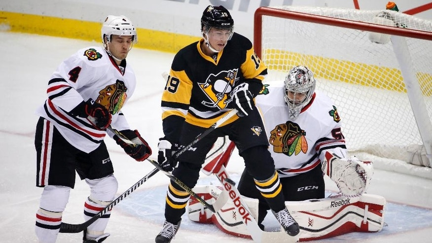 Pittsburgh Penguins' Beau Bennett (19) screens Chicago Blackhawks goalie Corey Crawford (50) with Niklas Hjalmarsson (4) defending during the first period of an NHL hockey game in Pittsburgh Wednesday, Jan. 21, 2015. Crawford blocked the shot. (AP Photo/Gene J. Puskar)
