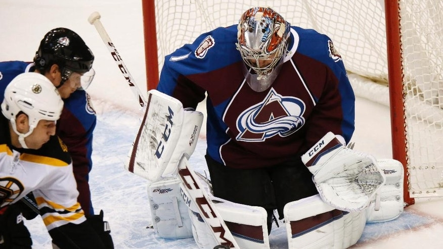 Colorado Avalanche goalie Semyon Varlamov, of Russia, right, makes a stop on a redirected shot off the stick of Boston Bruins left wing Milan Lucic, front left, as Avalanche defenseman Nick Holden looks on in the first period of an NHL hockey game Wednesday, Jan. 21, 2015, in Denver. (AP Photo/David Zalubowski)