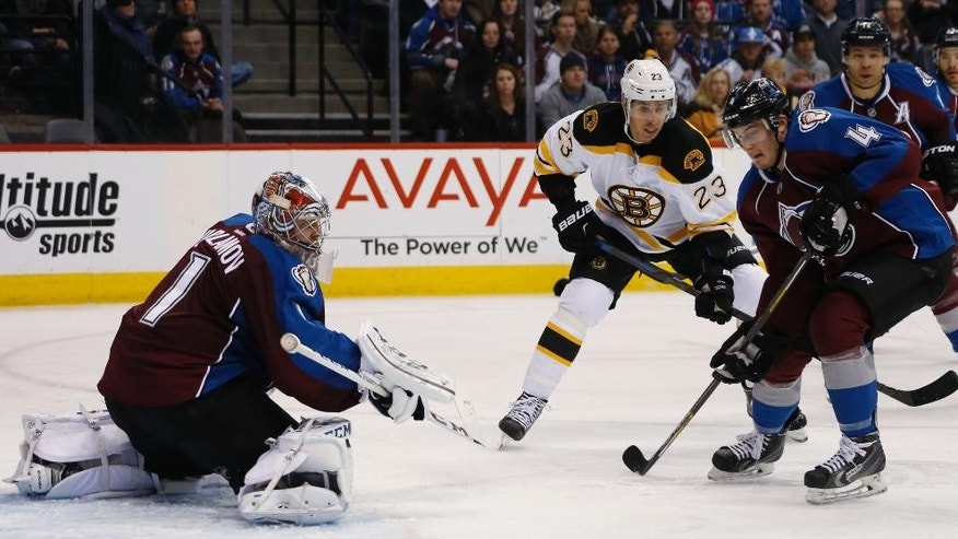 Colorado Avalanche defenseman Tyson Barrie, front right, clears the puck after a shot off the stick of Boston Bruins center Chris Kellyu, back right, was stopped by Avalanche goalie Semyon Varlamov, of Russia, in the second period of an NHL hockey game Wednesday, Jan. 21, 2015, in Denver. (AP Photo/David Zalubowski)