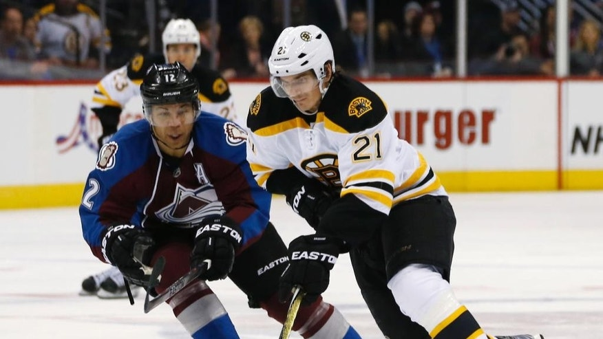 Boston Bruins right wing Loui Eriksson, front, of Sweden, drives down the ice with the puck as Colorado Avalanche right wing Jarome Iginla defends in the second period of an NHL hockey game Wednesday, Jan. 21, 2015, in Denver. (AP Photo/David Zalubowski)