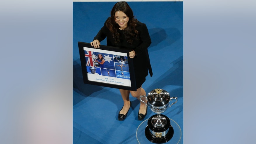 Retired defending Australian Open Champion Li Na receives a special presentation on Rod Laver Arena, prior to the night session of the Day 1 matches at the Australian Open tennis championship in Melbourne, Australia, Monday, Jan. 19, 2015. (AP Photo/Lee Jin-man)