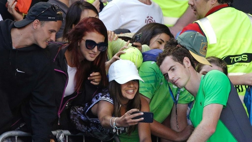 Andy Murray of Britain, right, poses for a fan's photo, after defeating Joao Sousa of Portugal during their third round match at the Australian Open tennis championship in Melbourne, Australia, Friday, Jan. 23, 2015. (AP Photo/Lee Jin-man)