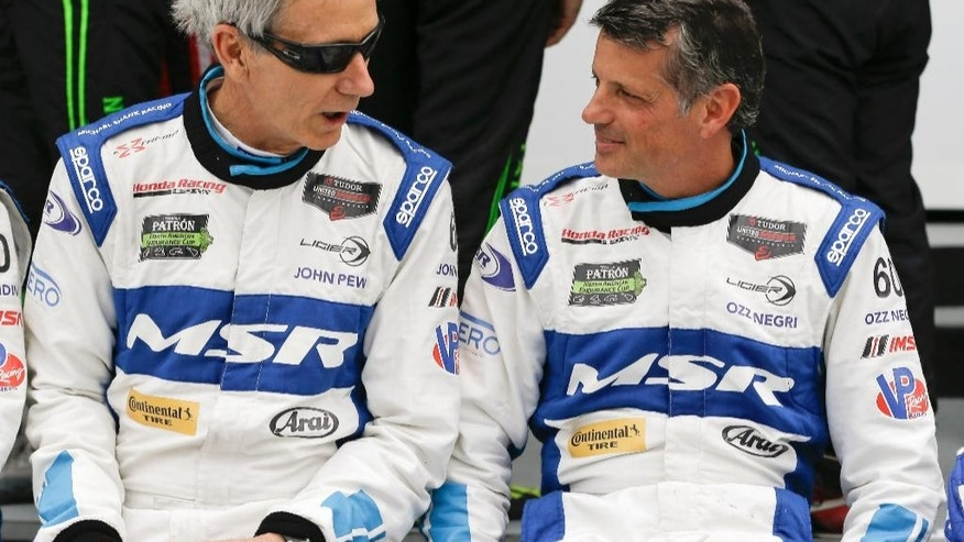 Co-drivers John Pew, left, and Oswaldo Negri, Jr., of Brazil, talk after a practice for  the IMSA 24 hour auto race at Daytona International Speedway, Friday, Jan. 23, 2015, in Daytona Beach, Fla. (AP Photo/John Raoux)