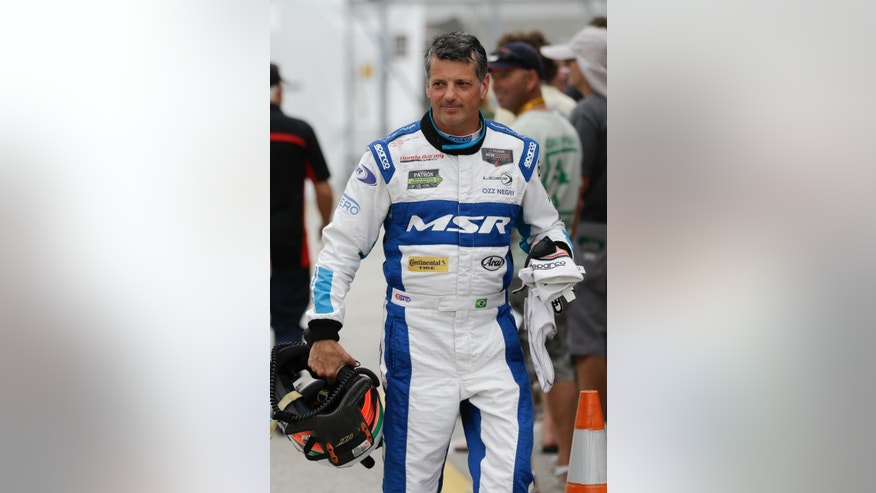 Oswaldo Negri, Jr., of Brazil, walks to his hauler after practicing for the IMSA 24 hour auto race at Daytona International Speedway, Friday, Jan. 23, 2015, in Daytona Beach, Fla. (AP Photo/John Raoux)