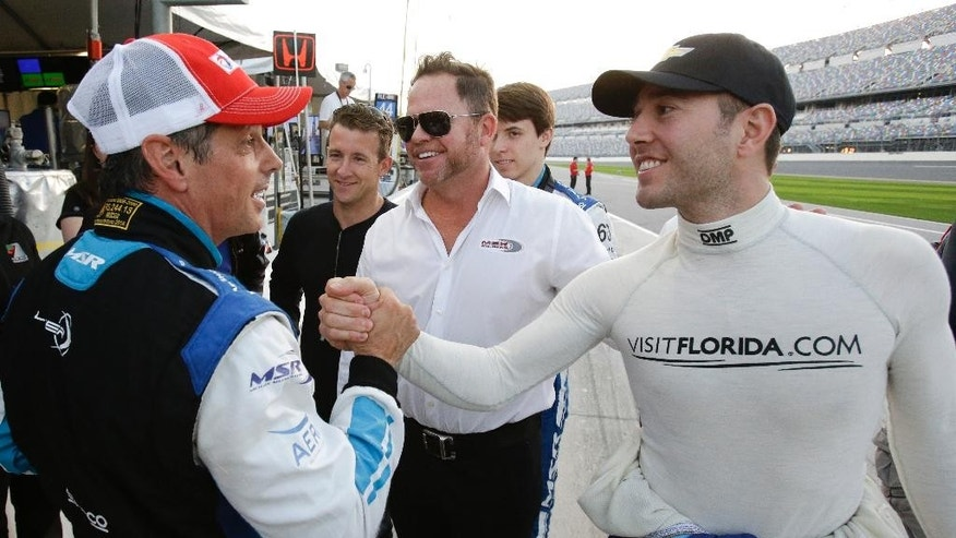 Oswaldo Negri, Jr., left, of Brazil, is congratulated by driver Michael Valiante, right, after winning the pole position for the IMSA 24-hour auto race as co-driver AJ Allmendinger, second from left, car owner Michael Shank, center, and co-driver Matt McMurry, second from right, celebrate on pit road at Daytona International Speedway, Thursday, Jan. 22, 2015, in Daytona Beach, Fla. (AP Photo/John Raoux)