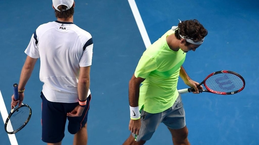 Roger Federer of Switzerland, right, walks away from Andreas Seppi of Italy, at the end of their third round match at the Australian Open tennis championship in Melbourne, Australia, Friday, Jan. 23, 2015. (AP Photo/Andy Brownbill)