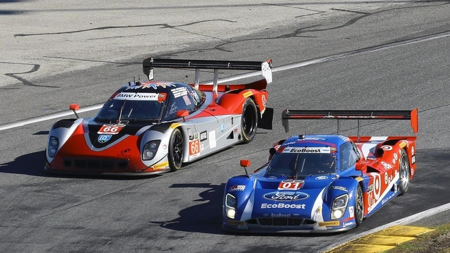 Race leader Scott Dixon (01) passes Shane Lewis (66) through a through a turn during the IMSA 24 hour auto race at Daytona International Speedway, Saturday, Jan. 24, 2015, in Daytona Beach, Fla. (AP Photo/David Graham)