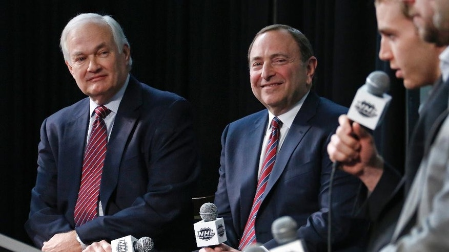 NHL Commissioner Gary Bettman, center, and NHL Player's Association executive director Donald Fehr, left, listen to Chicago Blackhawks' Patrick Kane, right, after announcing the return of the World Cup of Hockey in 2016 in Toronto, during a news conference at Nationwide Arena in Columbus, Ohio, before the NHL All-Star hockey skills competition, Saturday, Jan. 24, 2015. (AP Photo/Gene J. Puskar)