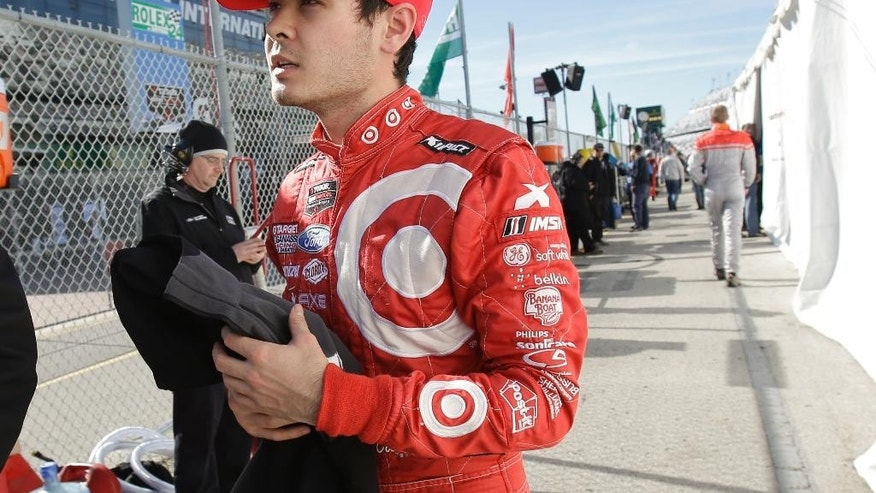Kyle Larson walks from pit road to his garage after driving in the IMSA 24 hour auto race at Daytona International Speedway, Sunday, Jan. 25, 2015, in Daytona Beach, Fla. (AP Photo/John Raoux)