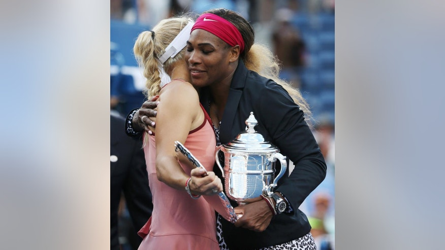 FILE - In this Sept. 7, 2014 file photo,  Serena Williams, right, hugs Caroline Wozniacki, of Denmark, after winning the championship match of the 2014 U.S. Open tennis tournament, in New York.  In their latest public display of friendship, Williams and Wozniacki posted a photo of getting their nails done before the Australian Open. The camaraderie, in a sport better known for its rivalries, has prompted discussion among players on what it's like in the locker room and behind-the-scenes with top tennis stars. (AP Photo/Mike Groll, File)