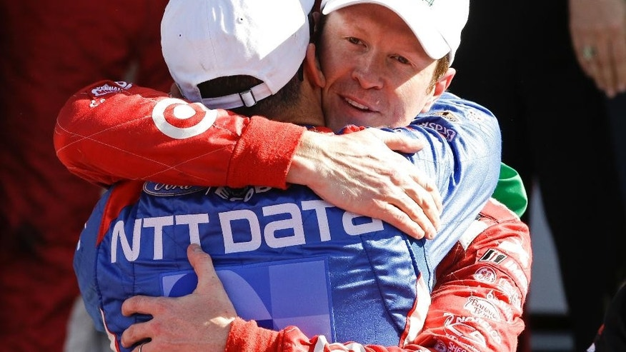 Co-drivers Tony Kanaan, left, of Brazil, and Scott Dixon, of New Zealand, celebrate after winning the IMSA 24 hour auto race at Daytona International Speedway, Sunday, Jan. 25, 2015, in Daytona Beach, Fla. (AP Photo/John Raoux)