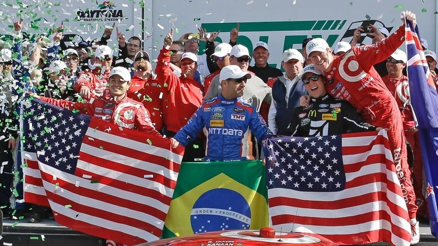 The winners of the IMSA 24 hour auto race, from left to right, Kyle Larson, Tony Kanaan, Jamie McMurray and Scott Dixon celebrate in Victory Lane at Daytona International Speedway, Sunday, Jan. 25, 2015, in Daytona Beach, Fla. (AP Photo/John Raoux)